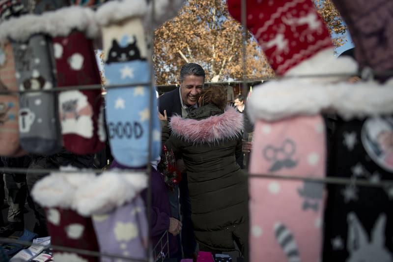 Xavier Garcia Albiol saluda a una mujer en su visita al mercado semanal en un barrio de El Prat de Llobregat (Barcelona)