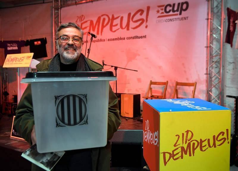 El candidato de la CUP a la Generalitat, Carles Riera, posa con una de las urnas de plástico empleadas en el referéndum del 1 de octubre, antes de participar en un mitin en Barcelona.
