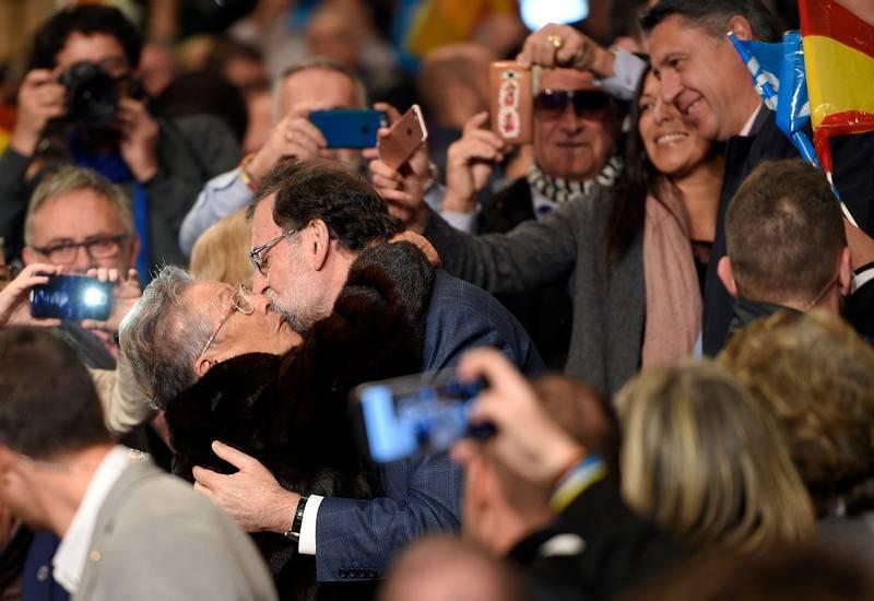 Rajoy, que ha tenido una alta participación en la campaña electoral, besa a una admiradora en un mitin en Salou.
