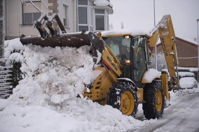 Una excavadora limpia una calle de nieve en la localidad cántabra de Reinosa