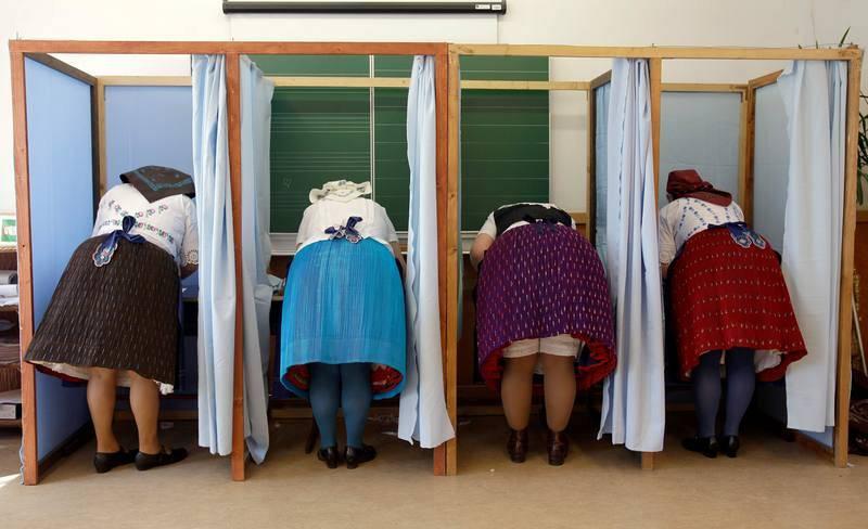 Mujeres vestidas con el traje tradicional húngaro preparan sus votos en un colegio electoral en Veresegyház, unos 30 kilómetros al este de Budapest