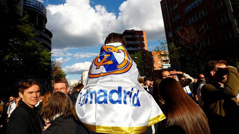 Un niño enfundado con la bandera del Real Madrid en los alrededores del estadio merengue.
