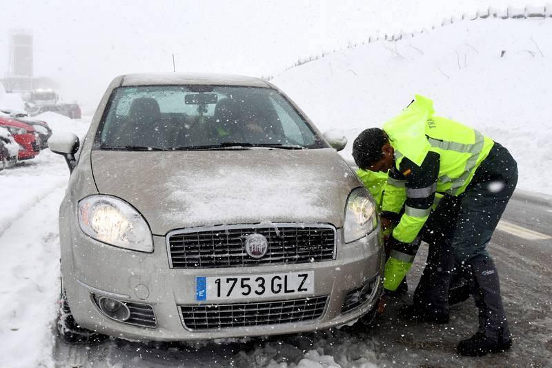 Un miembro de la Guardia Civil ayuda a poner las cadenas a un vehículo en el Puerto de Pajares