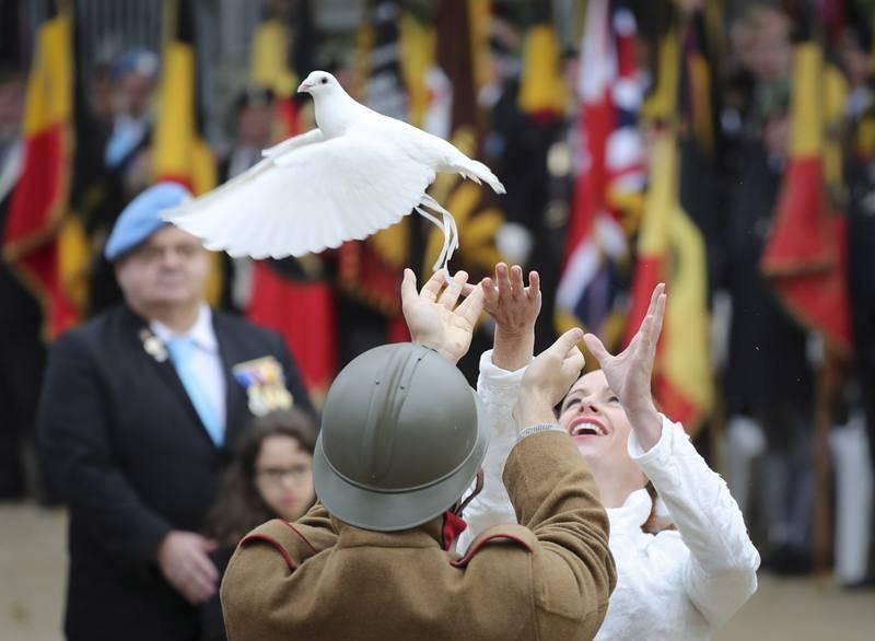 Dos personas lanzan una paloma durante una ceremonia en la tumba del soldado desconocido en la Columna de Congres, en Bruselas, Bélgica