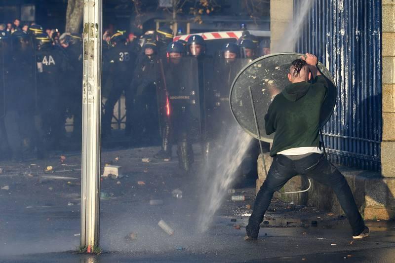 Un hombre se protege de la policía con una señal de tráfico en Quimper