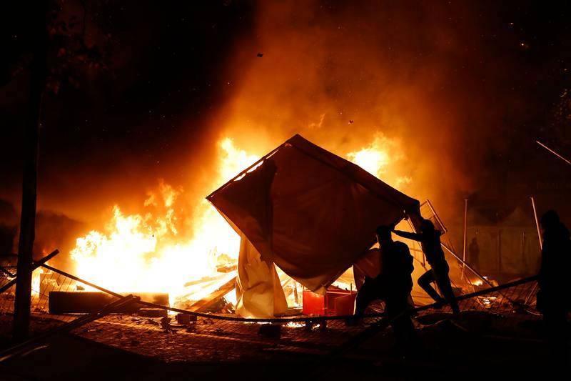 Un manifestante arroja material para avivar una hoguera en los Campos Elíseos