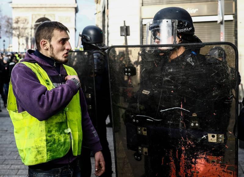 Un manifestante habla con un policía cerca de los Campos Elíseos