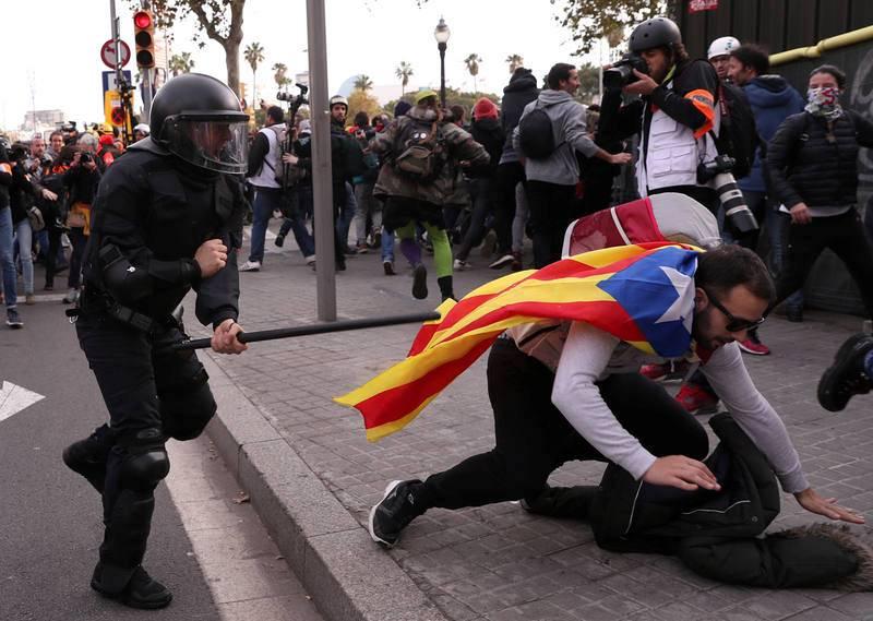 Un policía corre tras un manifestante durante la protesta en las inmediaciones de la Llotja de Mar de Barcelona, donde esta mañana se ha celebrado la reunión del Consejo de Ministros