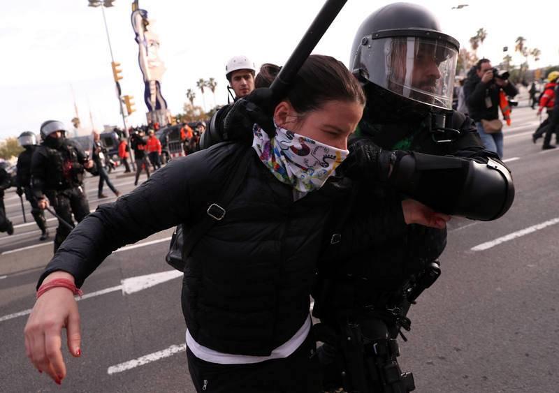 Un policía detiene a una manifestante durante la protestas  en el primer aniversario de las elecciones catalanas convocadas por el Gobierno de Mariano Rajoy con el artículo 155 de la Constitución