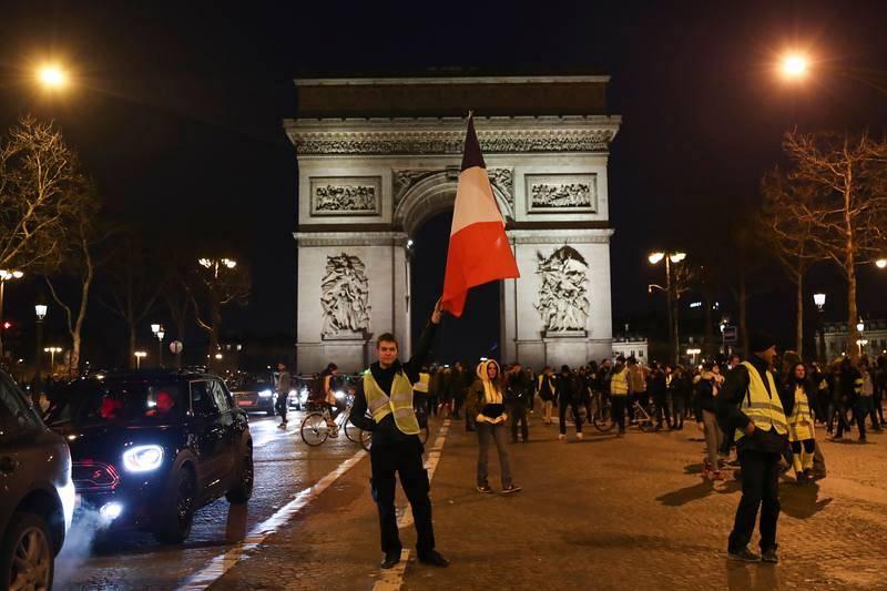 Un manifestante ondea la bandera de Francia en los Campos Elíseos en París