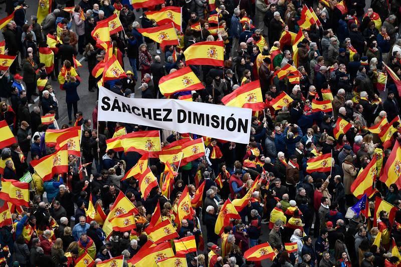 """Un grupo de asistentes a la concentración en la plaza de Colón porta una pancarta que reza """"Sánchez dimisión"""""""