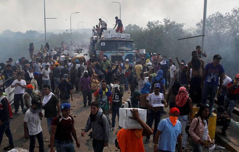 Seguidores de Guaidó descargan ayuda humanitaria de uno de los camiones que ha ardido en el puente Francisco de Paula Santander