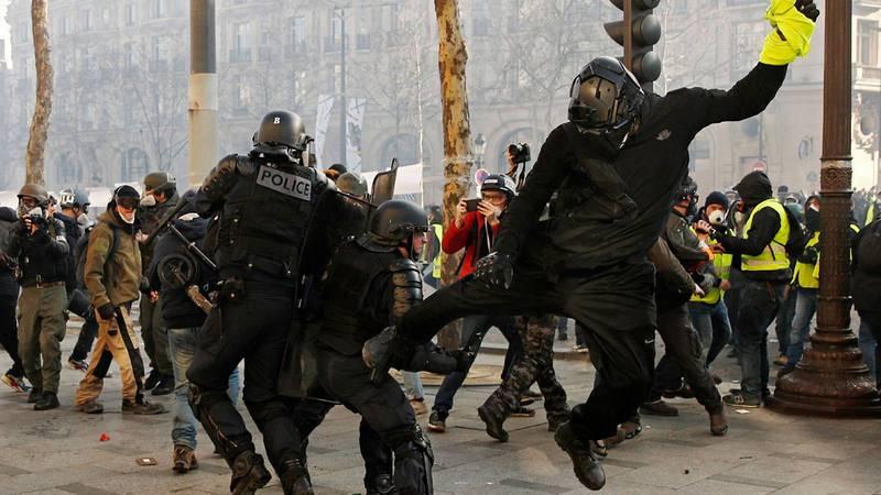 Un manifestante con el chaleco en la mano agrede a un policía en París