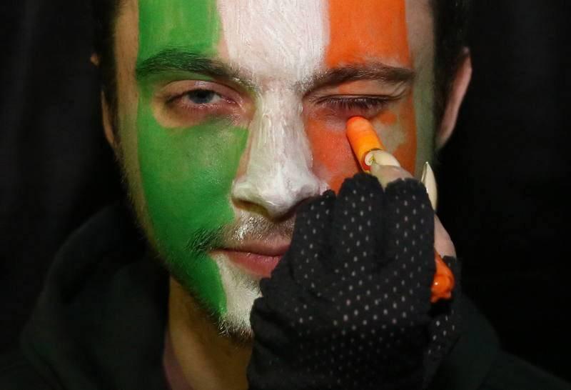 Un hombre se pinta la cara con los colores de la bandera de Irlanda para celebrar San Patricio en Minsk, Bielorrusia