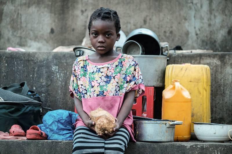 Una niña con un coco en sus manos en un refugio en el distrito de Búzi, provincia de Sofala, Mozambique