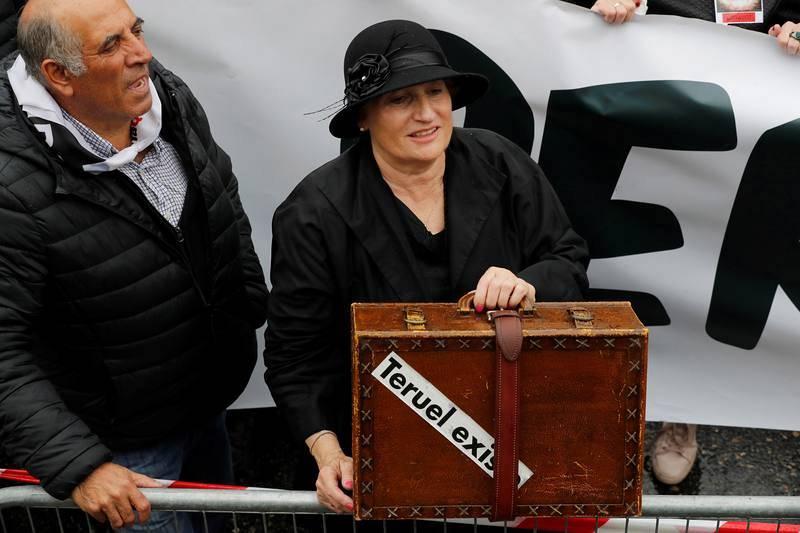 Una mujer con una maleta antigua en la manifestación