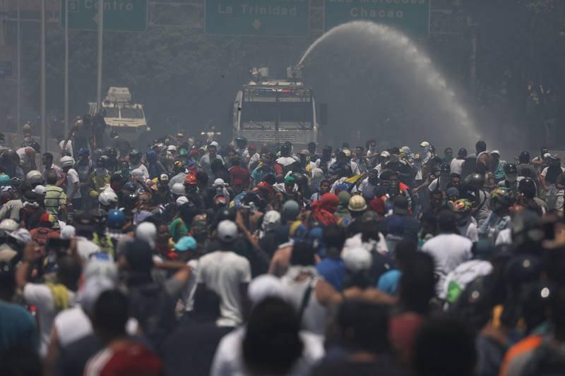 Simpatizantes del presidente de la Asamblea Nacional, Juan Guaidó, se enfrentan a las fuerzas oficialistas de las Fuerzas Armadas Bolivarianas, durante una manifestación en apoyo a su levantamiento contra el gobierno de Nicolás Maduro.
