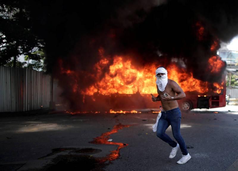 """Un manifestante de la oposición hace un gesto delante de un autobús en llamas, mientras sostiene una piedra en una calle cerca de la base aérea """"La Carlota"""" en Caracas."""