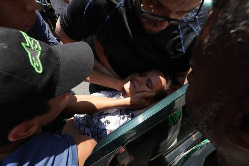 Simpatizantes del presidente de la Asamblea Nacional, Juan Guaidó, ayudan a una mujer herida por una bala en el estómago.