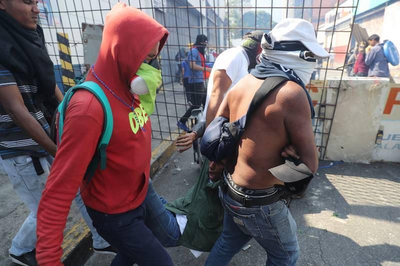 Simpatizantes de Guaidó ayudan a un herido durante una manifestación en apoyo a su levantamiento contra el gobierno de Nicolás Maduro este martes.