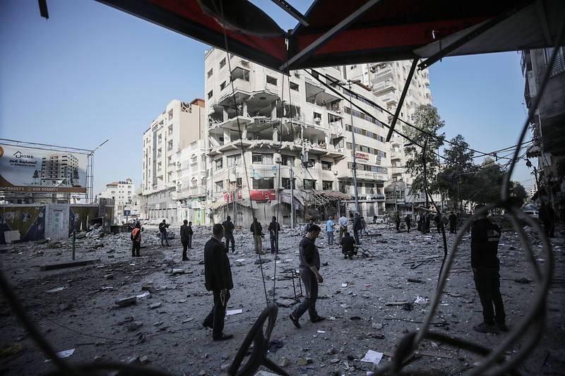 Varias personas inspeccionan un edificio dañado en Gaza tras un ataque aéreo israelí