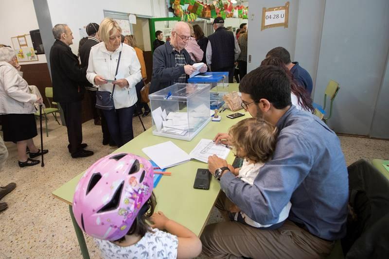 Un vocal de una mesa cuida de sus hijos durante la jornada electoral