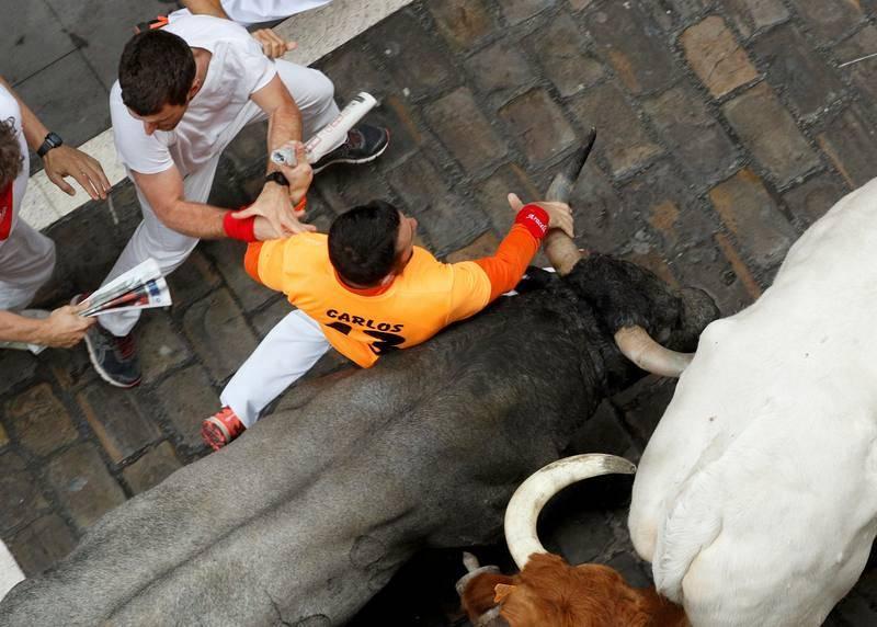 Otro mozo agarra el pitón del astado en Estafeta
