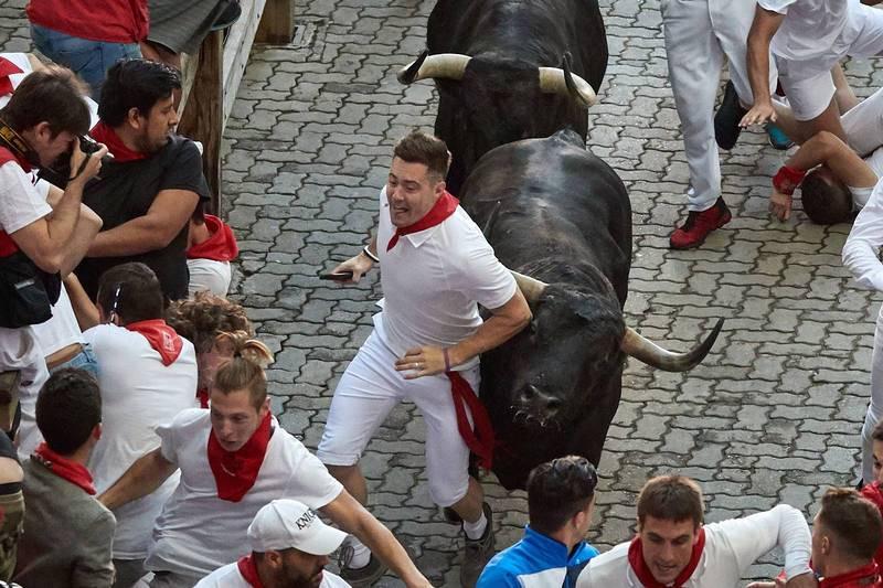 Un participante en el encierro delante de un toro