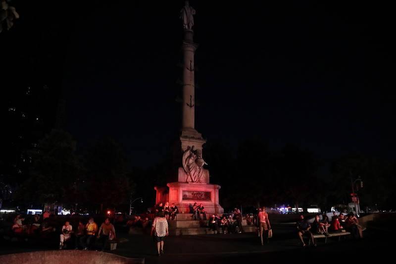 Ciudadanosesperando juntoal Columbus Circle de Manhattan la restauración del servicio eléctrico.