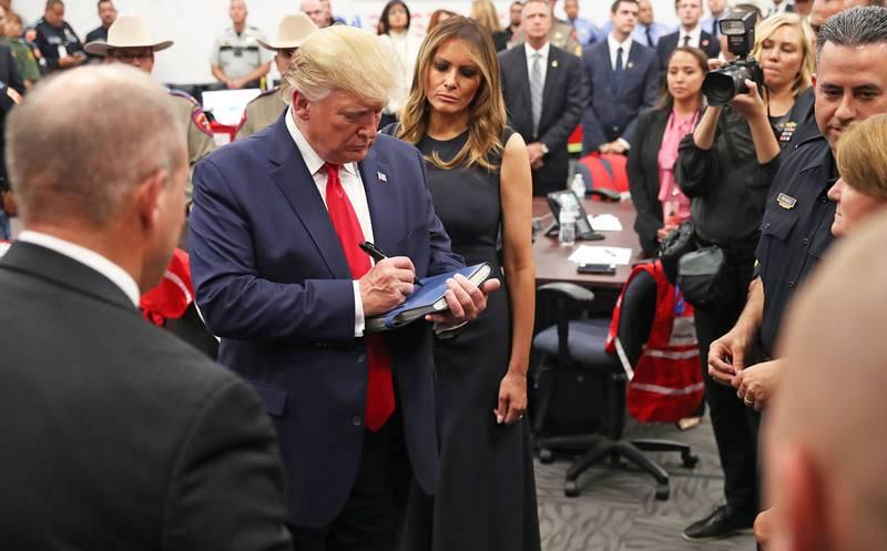 La primera dama, Melania Trump, observa como el presidente estadounidense, Donald Trump, firma un libro después de hablar con agentes de la ley durante su visita a El Paso tras el tiroteo