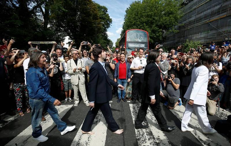 Un grupo de imitadores de The Beatles cruza el mítico paso de cebra de Abbey Road, de cuya imagen se cumple 50 años este jueves.