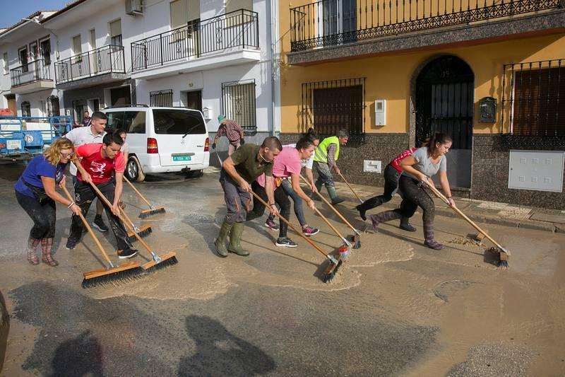 Vecinos de Villanueva del Trabuco, una de las zonas más afectadas por la gota fría en la provincia de Málaga, limpian las calles y retiran el barro tras la tromba de agua de la última noche