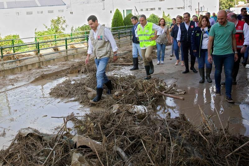 El presidente del Gobierno de Andalucía, Juanma Moreno, acompañado por el alcalde de Villanueva del Trabuco, José María García, entre otros, durante su visita a esta localidad andaluza, una de las zonas más afectadas por la gota fría