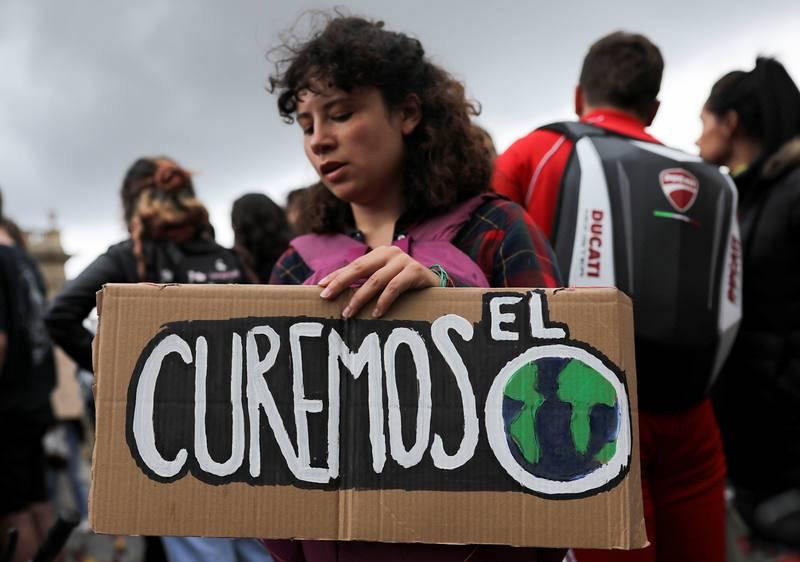 """Una mujer sostiene una pancarta en la que se lee """"Curemos el mundo"""""""