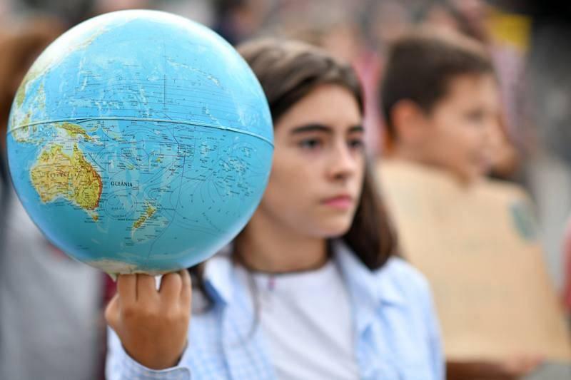 Una joven porta un globo terráqueo en la marcha por el clima que ha tenido lugar en Braga