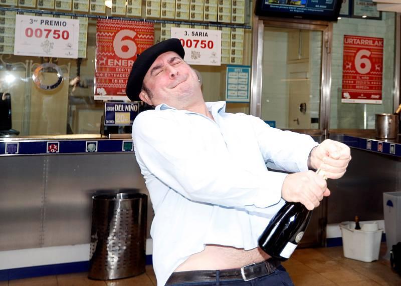 Juan Ortega Ezeiza, lotero de la administración 23 de Bilbao, abre una botella para celebrar el reparto del tercer premio de la lotería del número 00750, dotado con 500.000 euros por serie, que ha sido vendido en distintas localidades de los tres te