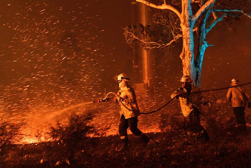 Los bomberos humedecen las brasas para proteger las casas cercanas