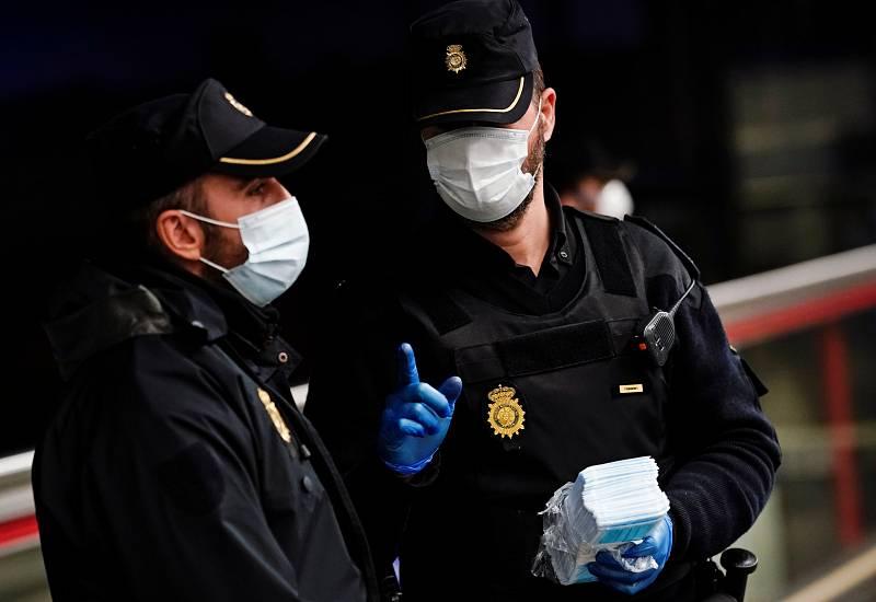 Dos policías reparten mascarillas en una estación de metro de Madrid durante el confinamiento.