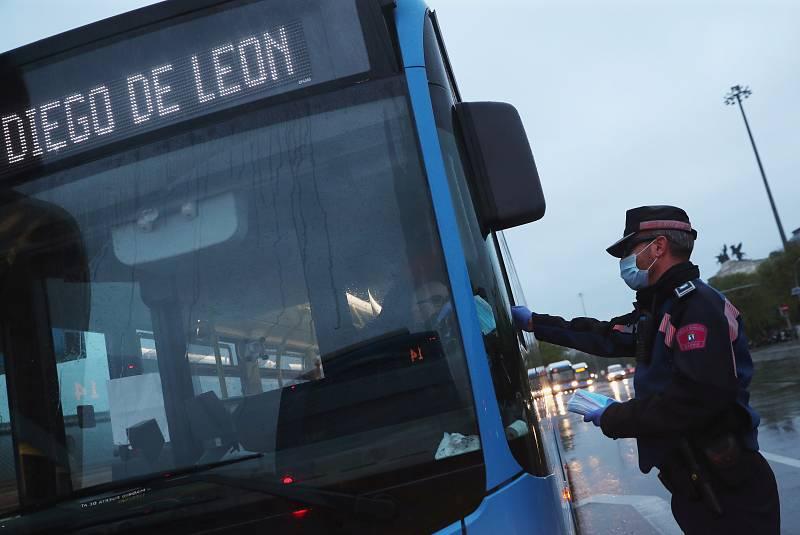 Un policía reparte una mascarilla a un conductor de autobús en Madrid.