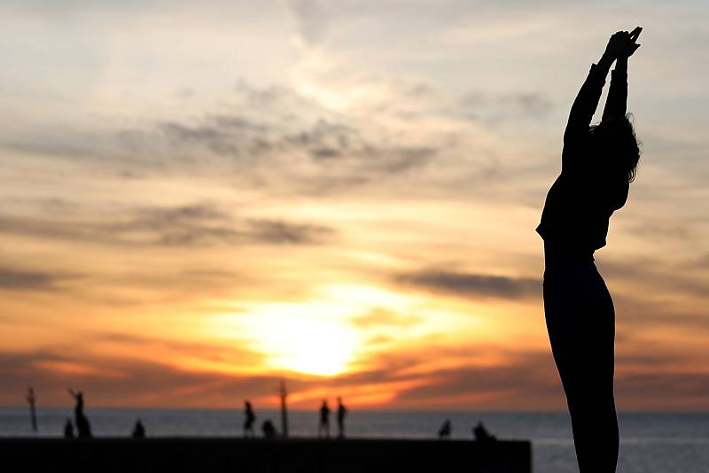 Una mujer hace deporte en la playa de la Barceloneta durante las horas que se permite el ejercicio individual al aire libre.
