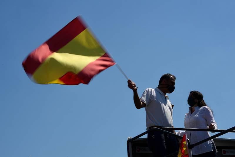 El secretario general de Vox, Javier Ortega Smith (i) alza una bandera de España en la Plaza de Colón de Madrid.