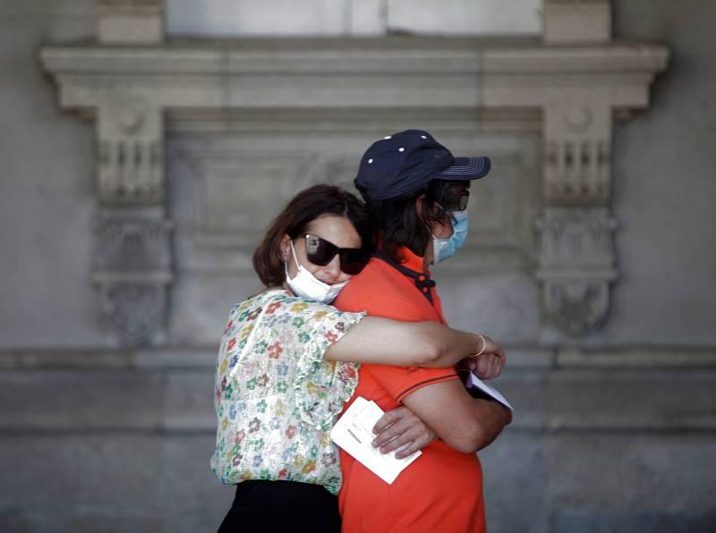 Dos personas aguardan en la fila para votar, este domingo en un colegio electoral de A Coruña con motivo de las elecciones autonómicas.