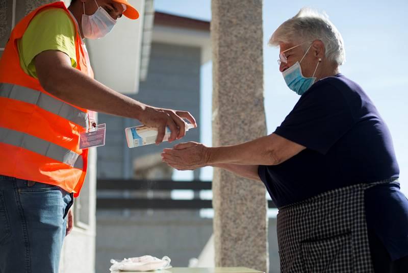 Una mujer se desinfecta las manos antes de votar en un colegio electoral de Requiás, Muiños (Ourense), este domingo con motivo de las elecciones autonómicas.