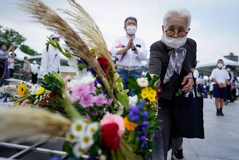 Una mujer ofrece una flor antes de rezar por las víctimas frente a un cenotafio en el Parque Conmemorativo de la Paz en Hiroshima.