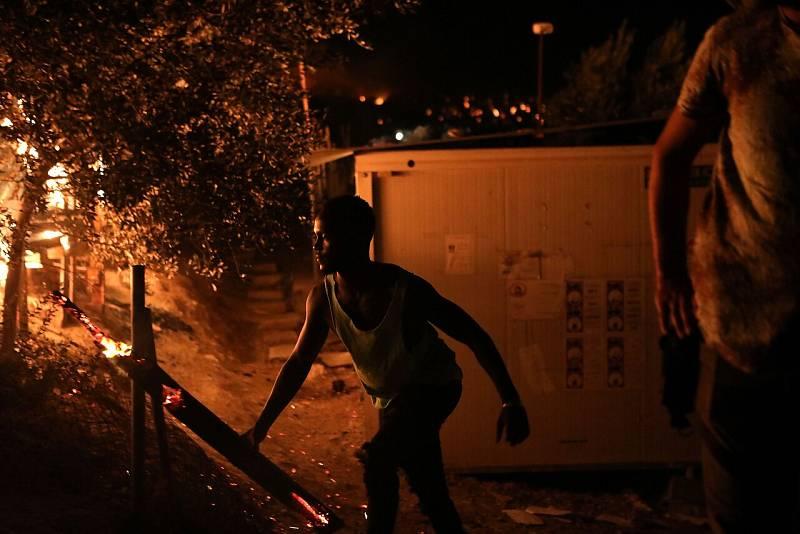 Un migrante mueve un tronco ardiendo en el campamento de Moria