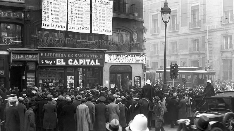 Multitud de personas se acercan a la Puerta del Sol para comprobar los números premiados en el Sorteo de Navidad.