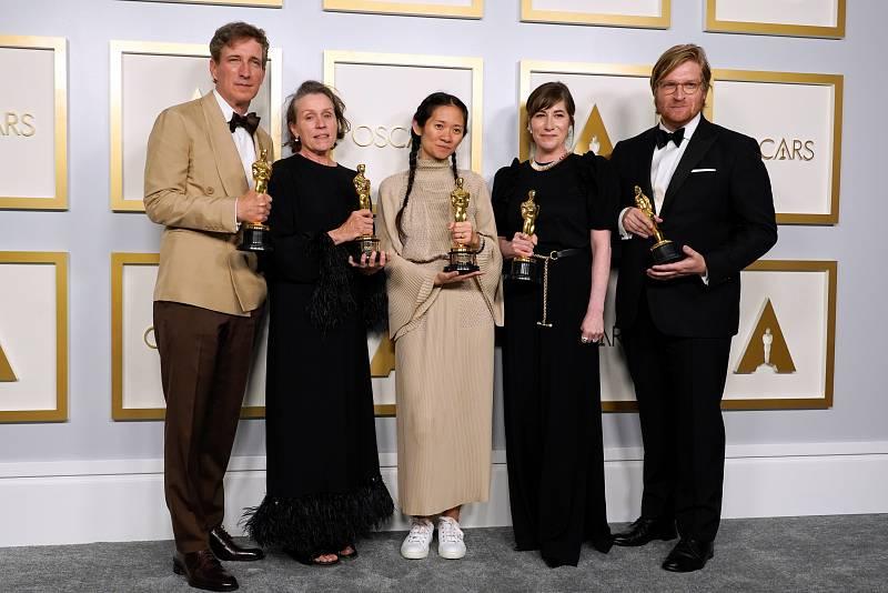 """Peter Spears, Frances McDormand, Chloe Zhao, Mollye Asher y Dan Janvey, ganadores del premio a la mejor película por """"Nomadland"""", posan en la sala de prensa de los Oscar."""