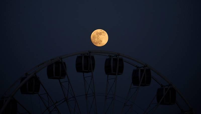 La Luna llena de mayoeste miércoles sobre las cabinas de una noria de feria en Córdoba.