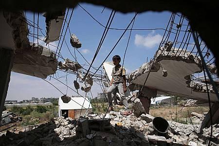 Un niño palestino juega entre los escombros un año después de la guerra de Gaza.