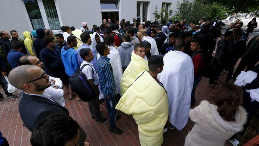 Migrantes y refugiados esperan a ser atendidos enfrente de la oficina de registro en el campo de refugiados de Friedland, Alemania